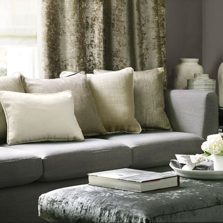 Clarke and Clarke -  Portfolio Fabric Collection - Oblong grey velvet footstool with plain grey three seater sofa, plain green and cream cushions, green velvet curtains, and ceramic vases