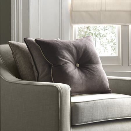 Clarke and Clarke -  Portfolio Fabric Collection - Armchair the colour of cement, with plain light, medium and dark grey cushions, with a plain cream blind