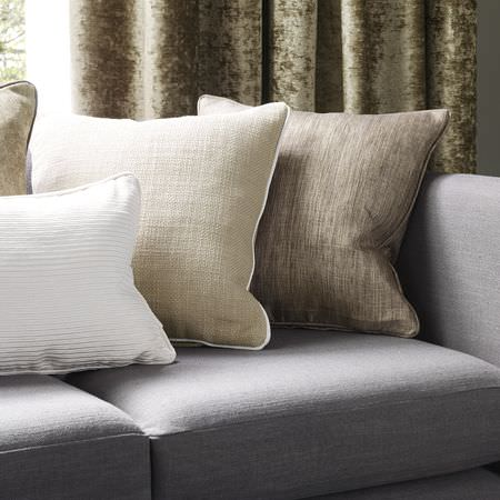 Clarke and Clarke -  Portfolio Fabric Collection - Beige and cream square scatter cushions with a rectangular ribbed white scatter cushion, on a grey sofa, with velour curtains in green