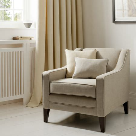 Clarke and Clarke -  Portfolio Fabric Collection - Light beige armchair with dark wood legs, a matching rectangular cushion, a square cream cushion and floor-length pale yellow curtains