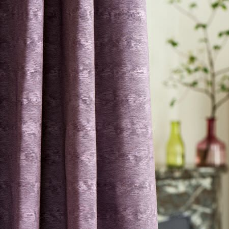 Clarke and Clarke -  Prima Fabric Collection - Curtains made from a plain pink-purple fabric, with one lime green glass bottle vase, and one red glass bottle shaped vase