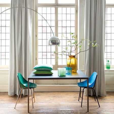Clarke and Clarke -  Prima Fabric Collection - Square table, moulded blue and green chairs, off-white curtains, a large arching lamp, big yellow vase, green cushions and moulded bowls