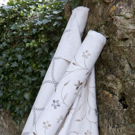 Clarke and Clarke -  Ribble Valley Fabric Collection - Bolt of white fabric embroidered with curving grey chains, and a bolt of white fabric embroidered with green and grey flowers and vines