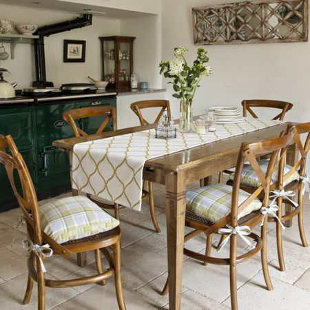 Clarke and Clarke -  Ribble Valley Fabric Collection - Brown wood dining table, six wooden chairs with tie-on checked seat cushions, and a white table runner with a gold curving design all over