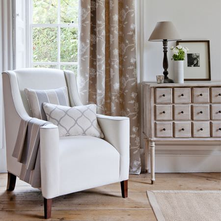 Clarke and Clarke -  Ribble Valley Fabric Collection - Distressed wood side table storage unit with small square drawers, white armchair, patterned cushions, floral curtains, lamp, white vase