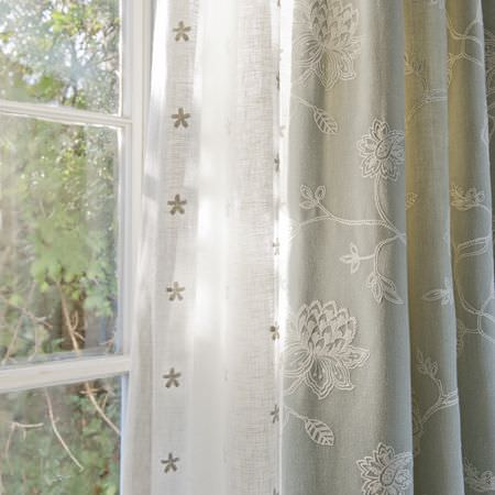 Clarke and Clarke -  Ribble Valley Fabric Collection - Very thin white fabric with tiny beige embroidered flowers, with light grey curtains with an embroidered lace effect cream floral pattern