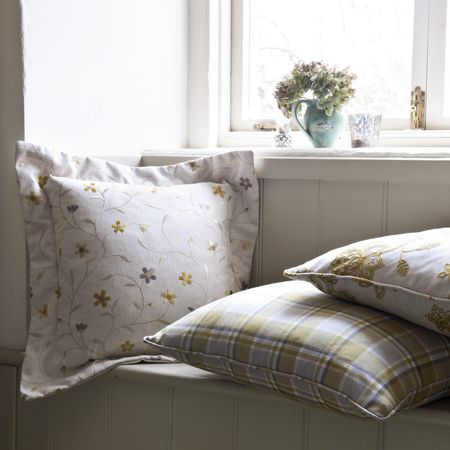 Clarke and Clarke -  Ribble Valley Fabric Collection - White cushion with fabric fringe embroidered with tiny green and grey flowers, with a green and grey checked cushion and a patterned cushion