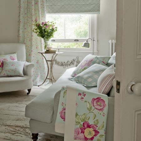 Clarke and Clarke -  Romance Fabric Collection - Rustic house with white upholstery and country style cushions and curtain decorated with pink roses