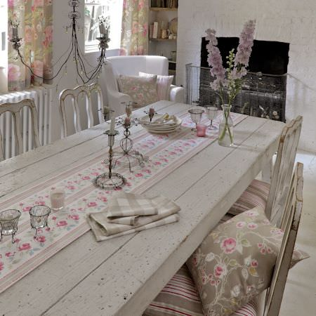 Clarke and Clarke -  Romance Fabric Collection - Rustic dining room setting with white and pink tablecloth with roses and striped cushioned chairs