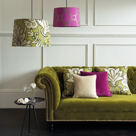 Clarke and Clarke -  Salon Fabric Collection - Green and magenta lampshades with a velour kiwi green sofa and plain and patterned green, magenta and cream cushions