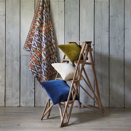 Clarke and Clarke -  Salon Fabric Collection - Three plain cushions in Royal blue, white and olive green, on a wooden stepladder, with tribal style patterned fabric