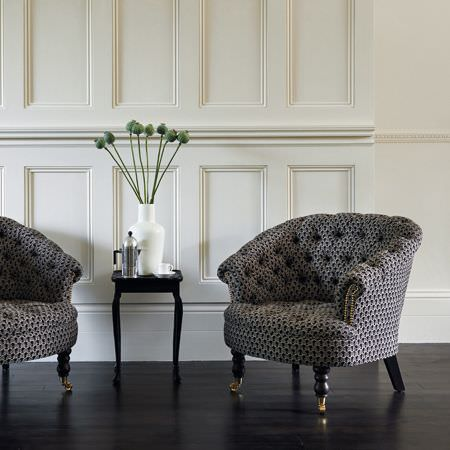 Clarke and Clarke -  Salon Fabric Collection - Padded tub chairs made with a small black and white pattern and black legs, with a black occasional table and a white vase