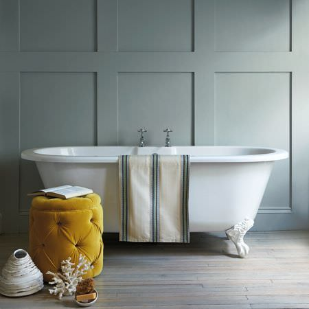 Clarke and Clarke -  Salon Fabric Collection - Cream and blue-grey striped fabric folded over the edge of a roll-top bath, with a mustard yellow padded footstool and coral