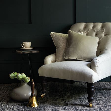 Clarke and Clarke -  Salon Fabric Collection - A bell and a grey vase with a small black and metal table with three legs, an off-white armchair and pale grey cushions