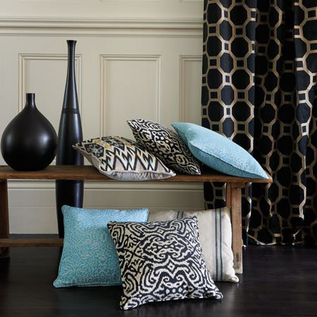 Clarke and Clarke -  Salon Fabric Collection - Black and pewter geometric print curtains with black, white and baby blue cushions, a wooden bench and two black vases