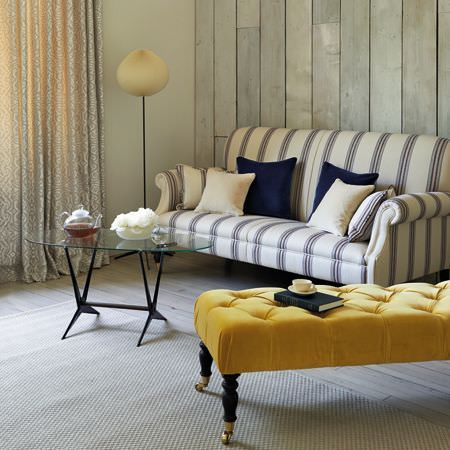 Clarke and Clarke -  Salon Fabric Collection - Big mustard yellow and black footstool with a blue and white striped sofa, blue and white cushions, and an oval glass table