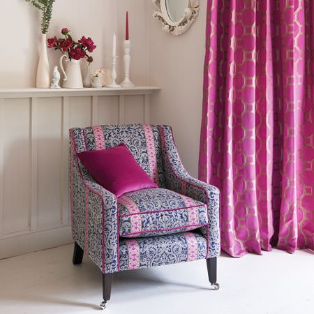 Clarke and Clarke -  Salon Fabric Collection - Pink, purple-grey and light grey patterned armchair with a hot pink cushion, pink and silver curtains and off-white vases