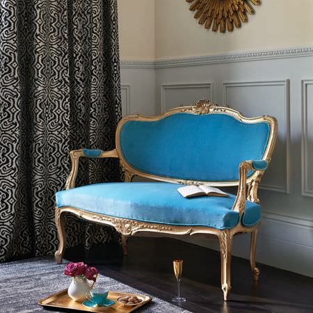 Clarke and Clarke -  Salon Fabric Collection - A gold wood frame to an aqua blue sofa, with black and silver patterned curtains, a gold tray and glass, and a blue teacup