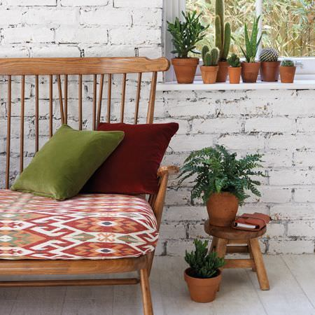 Clarke and Clarke -  Salon Fabric Collection - Terracotta pots, a small stool, a large wooden chair with a patterned white, red and orange seat, and red and orange cushions