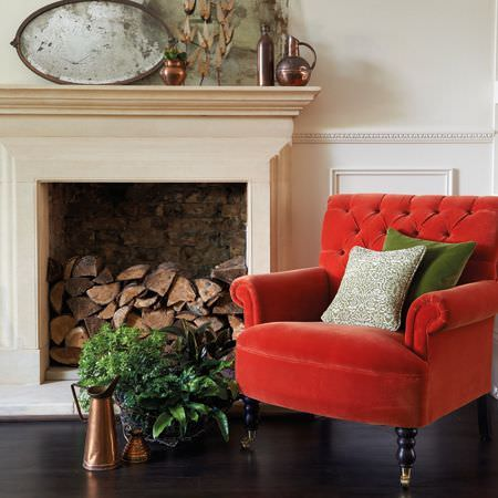 Clarke and Clarke -  Salon Fabric Collection - Fiery red armchair with black feet and green and white cushions, brass jugs and vases, foliage, an antique mirror and logs