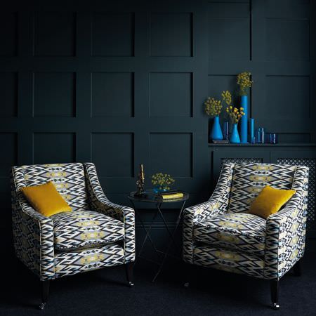 Clarke and Clarke -  Salon Fabric Collection - Two armchairs patterned in black, grey, yellow and white, with yellow cushions, a round black table and bright blue vases