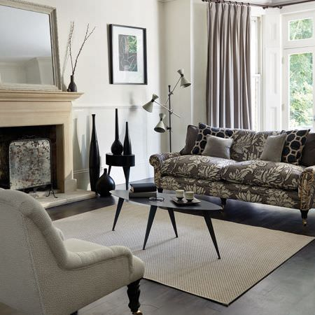 Clarke and Clarke -  Salon Fabric Collection - A black oval coffee table on a white rug, with a white armchair, a grey and white patterned sofa, and striped curtains