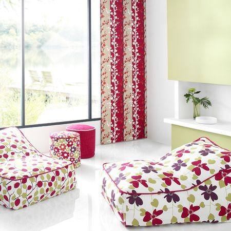 Clarke and Clarke -  Scandia Fabric Collection - beanbag reclinerswith red and green leaves and flowers design and a red and sandy curtain
