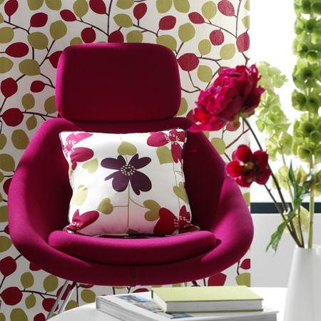 Clarke and Clarke -  Scandia Fabric Collection - Pillow with simple modern flower images on a purple upholstered chair, curtain with foliage pattern