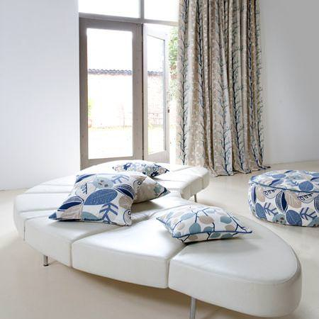 Clarke and Clarke -  Scandia Fabric Collection - Blue and white cushions and seating pad with foliage design with couch and a sandy white curtain