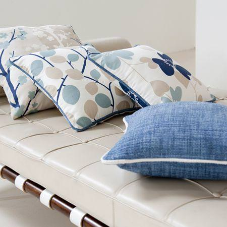 Clarke and Clarke -  Scandia Fabric Collection - Blue and white cotton cushions with flowers or plain monochrome on upholtered couch