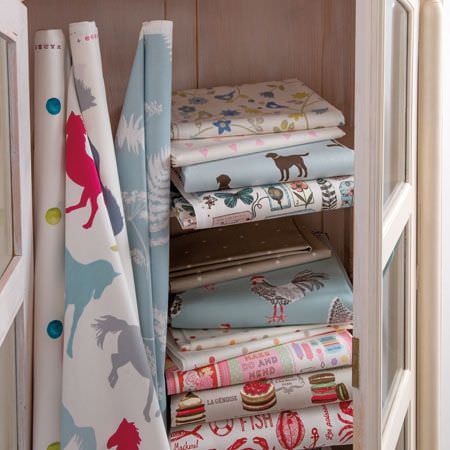 Clarke and Clarke -  Sketchbook Prints Fabric Collection - Various different animal, cake, floral and dot print fabrics on rolls or folded and stored in a white cupboard