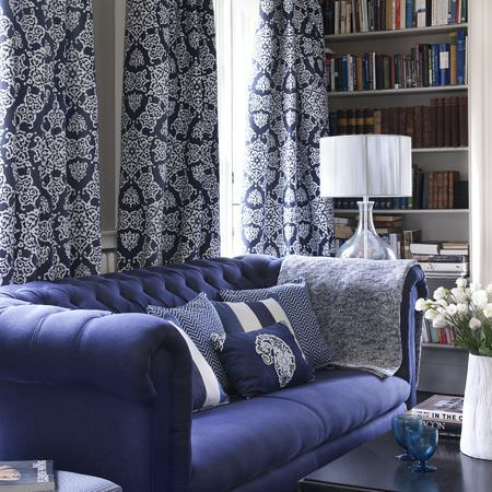 Clarke and Clarke -  Sonoma Fabric Collection - Large blue sofa with patterned and striped blue and white cushions, patterned curtains, a black table, a white table lamp, and a white vase
