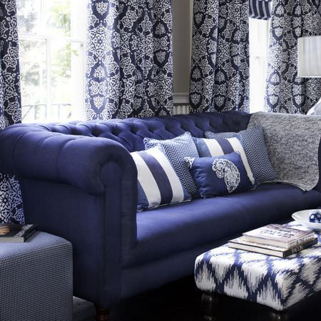 Clarke and Clarke -  Sonoma Fabric Collection - Blue and white rough diamond pattern footstool with plain blue sofa, scatter cushions, blue and white curtains, and blue and white fabric