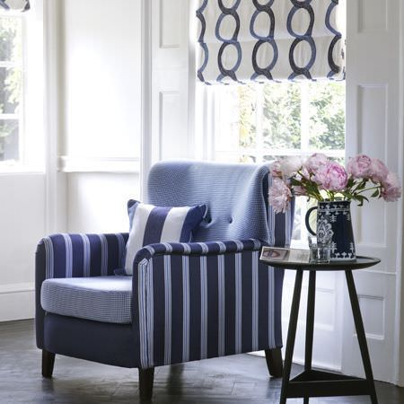 Clarke and Clarke -  Sonoma Fabric Collection - Blue armchair with plain back, striped sides, pale seat, with a wide striped cushion, printed blinds, black table and a blue and white vase