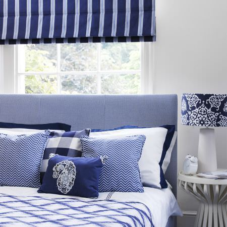 Clarke and Clarke -  Sonoma Fabric Collection - Bed with blue and white checked headboard, plain, patterned and checked cushions, a throw, striped blind, wood side table and patterned lamp