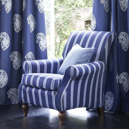 Clarke and Clarke -  Sonoma Fabric Collection - White paisley shapes on royal blue curtains, behind a blue and white striped armchair with a blue and white zigzag print cushion