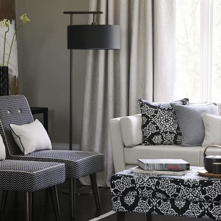 Clarke and Clarke -  Sonoma Fabric Collection - Two monochrome zigzag chairs, a white sofa, a black and white patterned footstool, matching cushions, plain curtains and a black floor lamp