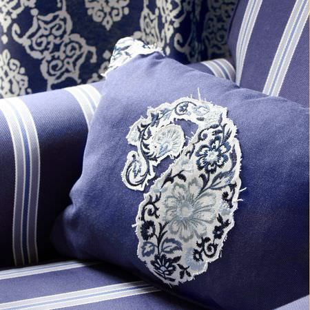 Clarke and Clarke -  Sonoma Fabric Collection - Royal blue cushion with a large floral blue and white paisley shape appliqued on, with a blue and white striped sofa and patterned fabric