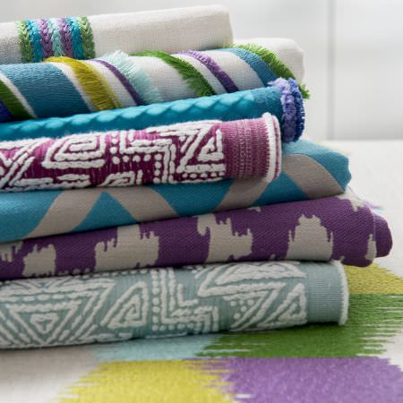 Clarke and Clarke -  South Beach Fabric Collection - Folds of assorted patterned and textured fabrics in colours such as cream, grey, purple, blue and green