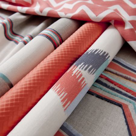 Clarke and Clarke -  South Beach Fabric Collection - Rolls and folds of fabric with orange zigzags, textured lines, printed patterns, embossed orange textures, and embroidered coloured stripes