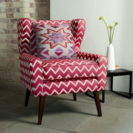 Clarke and Clarke -  South Beach Fabric Collection - Large zigzag print chair in red and white, with a multicoloured Aztec print cushion, black side table and an elegant white vase