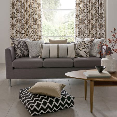 Clarke and Clarke -  South Beach Fabric Collection - Monochrome zigzag seat cushion, grey sofa, cream/beige Aztec print cushions and curtains, coordinating cushions, oval wood table, cream vase