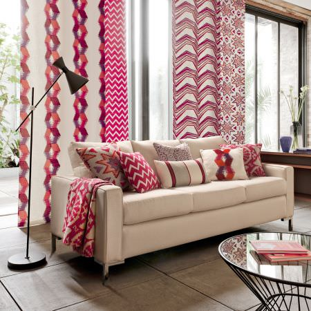 Clarke and Clarke -  South Beach Fabric Collection - Fabrics with different red and cream patterns, matching cushions, cream sofa, black anglepoise floor lamp, metal table with round glass top