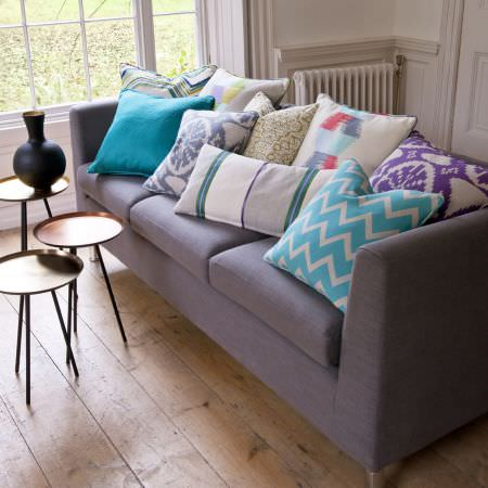 Clarke and Clarke -  South Beach Fabric Collection - Three small, round copper tray side tables of differing heights, with a black vase, mauve-grey sofa and nine multicoloured scatter cushions