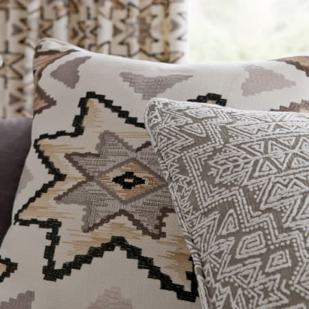 Clarke and Clarke -  South Beach Fabric Collection - Cushion with a large cream, beige, grey and black Aztec design, matching curtains, and a grey cushion with a cream embroidered Aztec design
