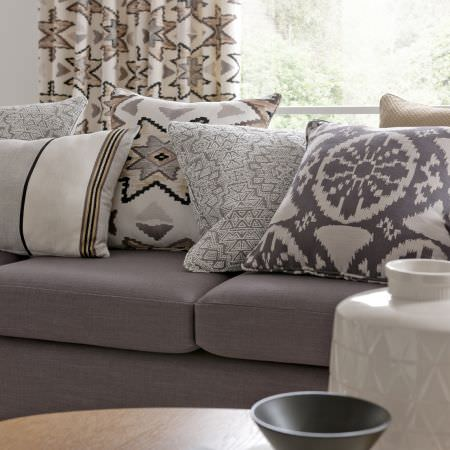 Clarke and Clarke -  South Beach Fabric Collection - Geometric print and striped cushions in grey, cream and beige, on a grey sofa, with patterned curtains, wood table, cream vase and grey bowl
