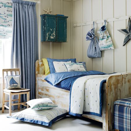 Clarke and Clarke -  Storybook Fabric Collection - A distressed light wood bed and chair with blue and white dotted bedding and throws, cushions with dots and nautical themes