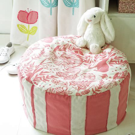 Clarke and Clarke -  Storybook Fabric Collection - A circular pink and white striped and patterned footstool withsimple floral curtains, and a stuffed bunny rabbit toy