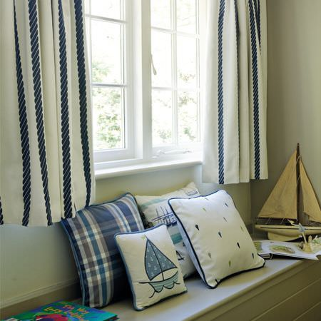Clarke and Clarke -  Storybook Fabric Collection - Short navy and white striped curtains with sailboat themed, checked and dotted blue and white cushions, and a toy boat