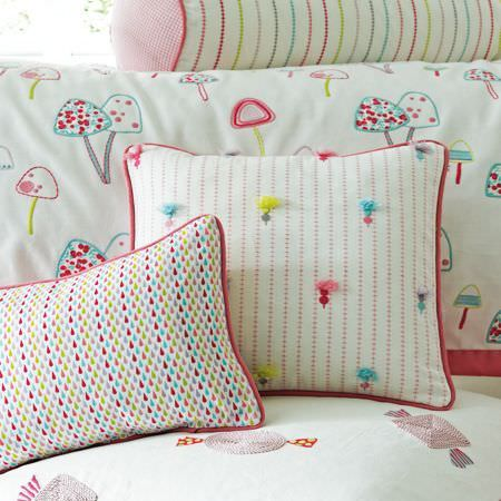 Clarke and Clarke -  Storybook Fabric Collection - Dots, lines, toadstools and sweets patterning white cushions and bedding in light shades of pink, green, blue and grey
